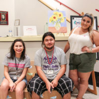 Victor Seguin (middle) with his former We 'Ced Youth Media mentor Crystal Rivera (right) and We 'Ced reporter Hannah Esqueda (left) at the Multicultural center in Merced Calif.